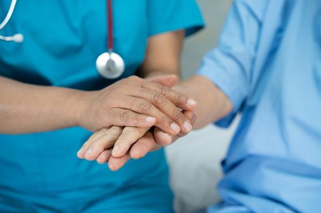 Trzymając się za ręce azjatycki starszy kobieta pacjent z miłością
