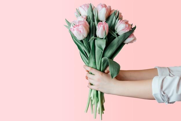 Trzymając się za ręce bukiet różowych tulipanów na różowej ścianie