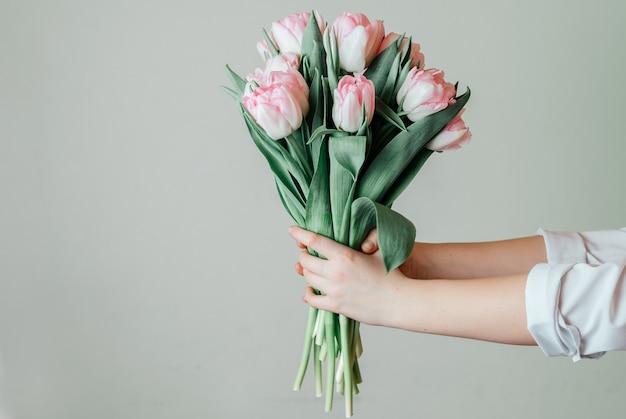 Trzymając się za ręce bukiet różowych tulipanów
