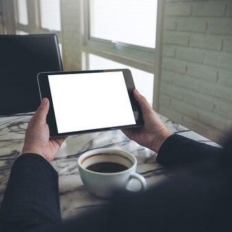 Trzymając się za ręce czarny tablet pc z pusty biały ekran i filiżankę kawy