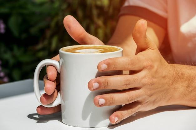 Trzymając się za ręce filiżankę kawy