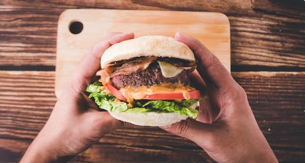Trzymając się za ręce gotowego do spożycia hamburgera w restauracji