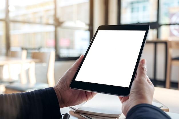 Trzymając się za ręce i używając czarnego komputera typu tablet z pustym białym ekranem pulpitu podczas pracy na notebookach w biurze