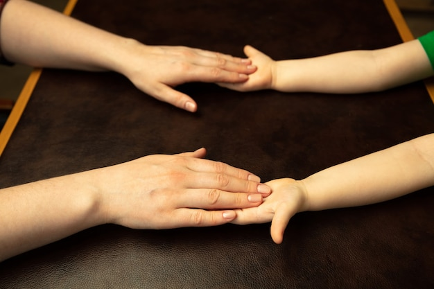 Trzymając się za ręce, klaszcząc jak przyjaciele. bliska strzał rąk kobiet i dzieci robienie różnych rzeczy razem. rodzina, dom, edukacja, dzieciństwo, koncepcja charytatywna. matka i syn lub córka, bogactwo.