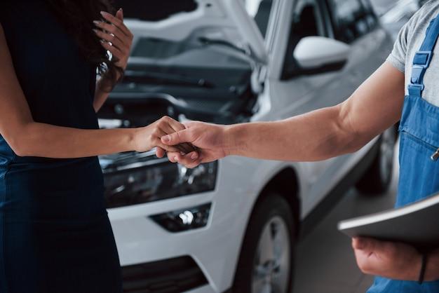 Trzymając się za ręce. kobieta w salonie samochodowym z pracownikiem w niebieskim mundurze zabierająca naprawiony samochód z powrotem.