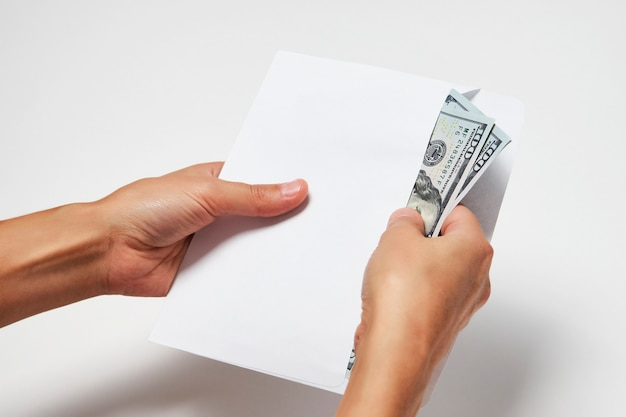Trzymając się za ręce kopertę z pieniędzmi dolara na białym tle. ręka kobiety wyjmuje pieniądze z koperty, zbliżenie. koncepcja korupcji łapówki, wynagrodzenia, zarobków i oszczędności