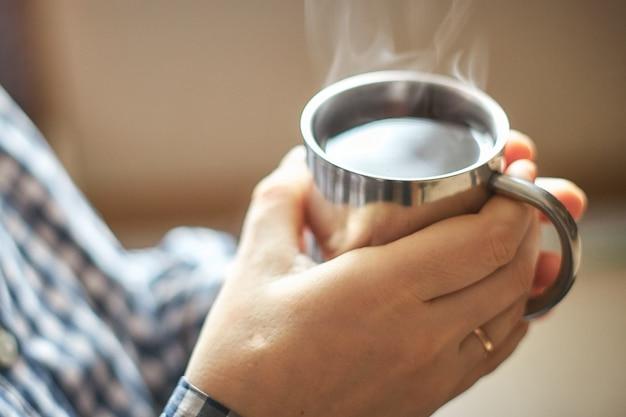 Trzymając się za ręce kubek z gorącą herbatą