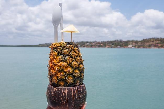 Trzymając się za ręce napój ananasowy z tłem plaży.