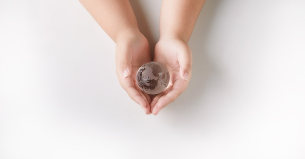 Trzymając się za ręce ochrony globe glass. pojęcie środowiska