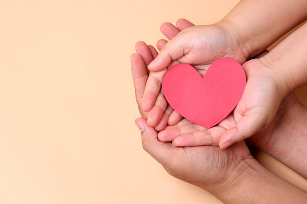 Trzymając się za ręce papier czerwone serce, pojęcie zdrowia w rodzinie.