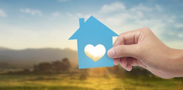 Trzymając się za ręce papierowy dom, dom rodzinny i ochrona koncepcji ubezpieczenia