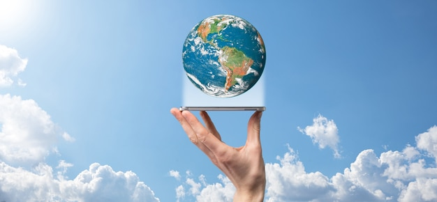 Trzymając się za ręce planetę, ziemię na powierzchni natury błękitne niebo z pięknymi białymi chmurami i światłem słonecznym