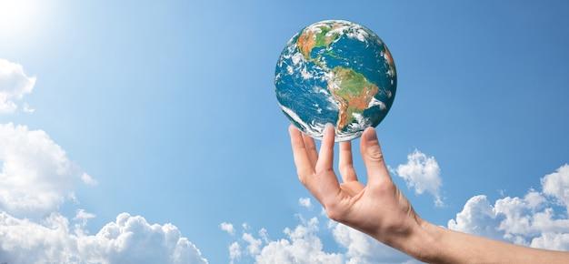 Trzymając się za ręce planetę, ziemskie niebo z pięknymi białymi chmurami i światłem słonecznym. koncepcja podtrzymywania ziemi. elementy tego zdjęcia zostały umeblowane