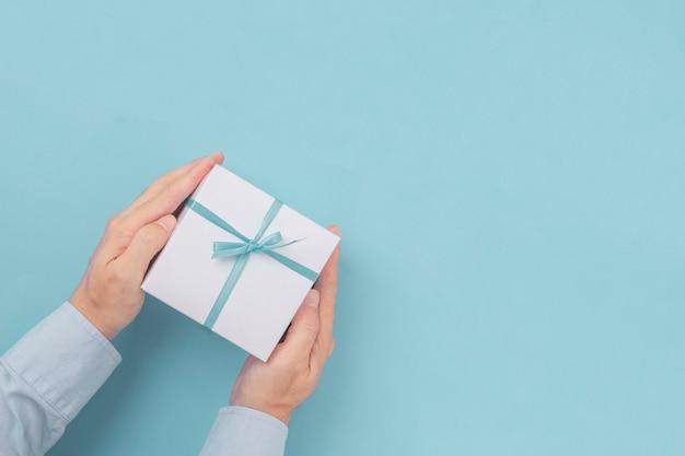 Trzymając się za ręce pudełko z niebieską kokardą z miejsca na kopię w papierze rzemiosła. widok z góry, leżał płasko