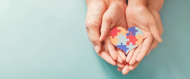 Trzymając się za ręce puzzle układanki w kształcie serca, światowy dzień świadomości autyzmu