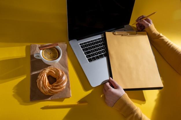 Trzymając się za ręce schowek w pobliżu laptopa, ciasta i filiżankę herbaty, widok z góry.