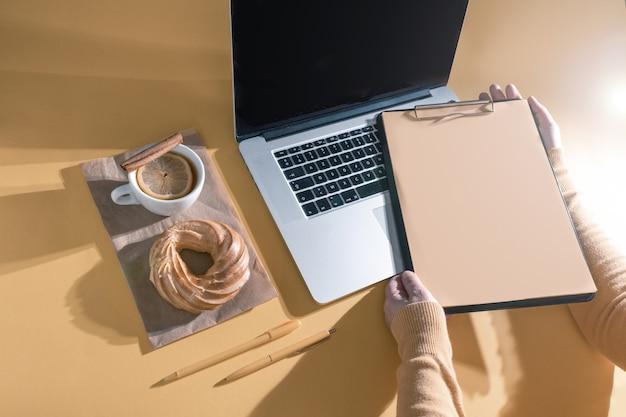 Trzymając się za ręce schowek w pobliżu laptopa, ciasta i filiżanki herbaty