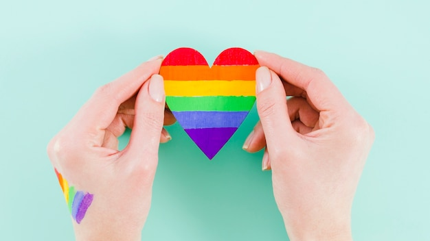 Trzymając się za ręce serce z kolorami flagi dzień dumy