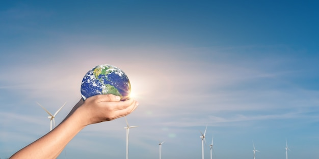Trzymając się za ręce świata, ziemi na tle pola turbiny wiatrowej. pojęcie światowej ochrony środowiska i energii odnawialnej. elementy tego obrazu dostarczone przez nasa