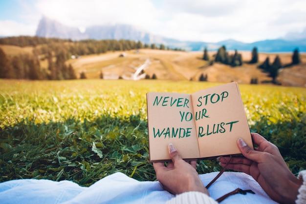 """Trzymając się za ręce tekst strony """"nigdy nie przestawaj swojej wędrówki"""" z krajobrazem górskiej przyrody w tle"""