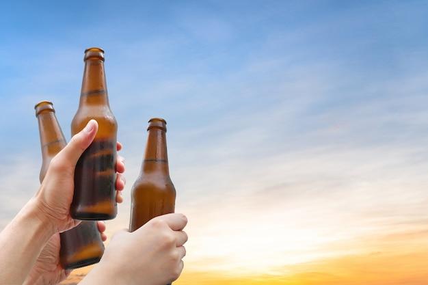 Trzymając się za ręce trzy butelki piwa. sukces świętowania picia piwa.