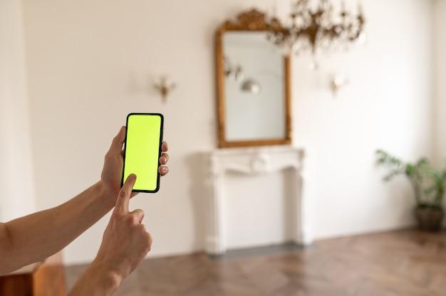 Trzymając smartfon z zielonym ekranem chroma key, oglądając zawartość bez dotykania lub przesuwania gadżetów i ...