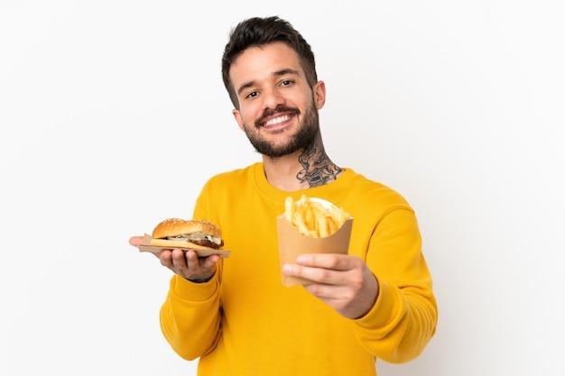 Trzymając smażone frytki i cheeseburgera na białym tle