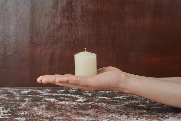 Trzymając świecę w dłoni.