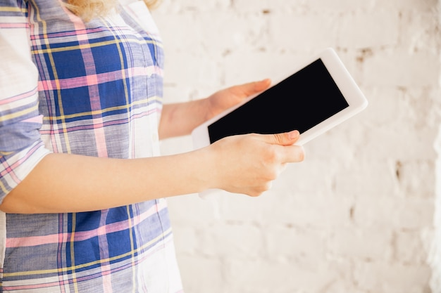 Trzymając tablet. zbliżenie na kaukaski kobiece ręce, pracując w biurze. pojęcie biznesu, finansów, pracy, zakupów online lub sprzedaży. miejsce na reklamę. edukacja, komunikacja niezależna.