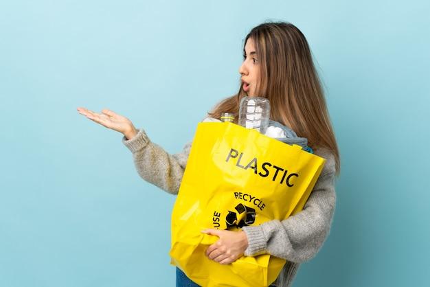 Trzymając torbę pełną plastikowych butelek do recyklingu na izolowanych niebieski gospodarstwa copyspace wyimaginowany na dłoni