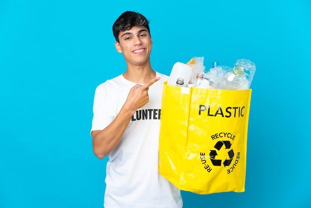 Trzymając torbę pełną plastikowych butelek do recyklingu na niebiesko, wskazując w bok, aby przedstawić produkt
