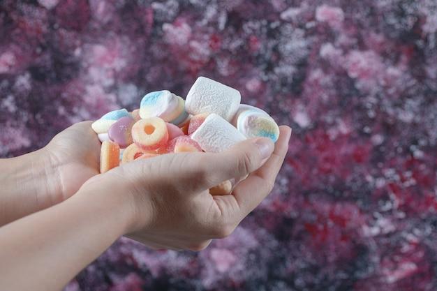 Trzymając w dłoni cukierki marshmallow.