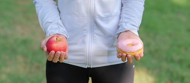 Trzymając w ręku czerwone jabłko i pączek