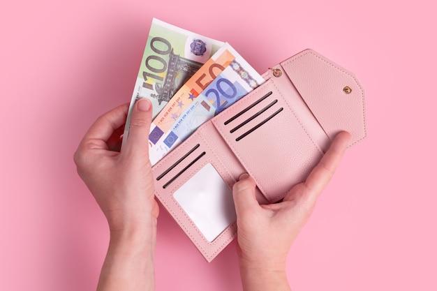 Trzymający różowy skórzany portfel z pieniędzmi euro w rękach, pojęcie pieniędzy, finanse, zakupy, gotówka
