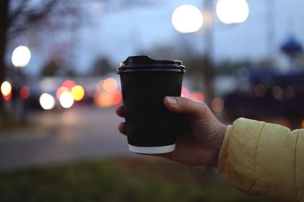 Trzymam filiżankę kawy i podnoszę rękę, żeby zrobić zdjęcie z rozmytym tłem. czarna filiżanka kawy bez logo w dłoni.