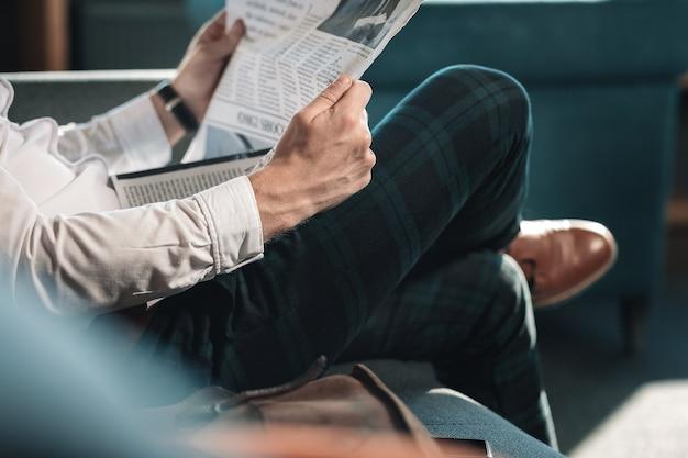 Trzymam gazetę. zbliżenie na inteligentny udany dojrzały mężczyzna trzymając gazetę podczas czytania w godzinach porannych