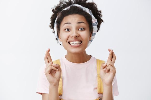 Trzymam kciuki za ciebie. portret przystojnej, dopingującej, ładnej afroamerykanki w opasce i kombinezonie, uśmiechającej się szeroko, wyrażając życzenie, błagając o szczęście nad szarą ścianą