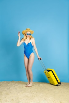 Trzymanie biletów. szczęśliwa młoda kobieta z torbą przygotowaną do podróży na niebieskim tle studia. pojęcie ludzkich emocji, wyraz twarzy, wakacje, weekend. lato, morze, ocean, alkohol.
