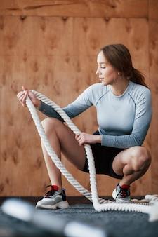 Trzymanie liny do ćwiczeń. sportive młoda kobieta ma dzień fitness na siłowni w godzinach porannych