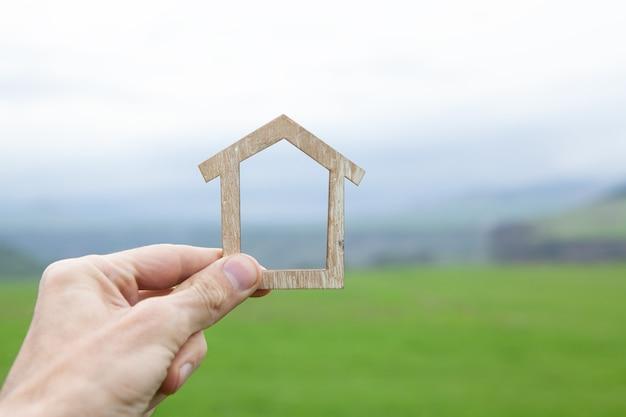 Trzymanie małego domku na scenie natury