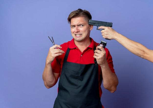 Trzymanie pistoletu w świątyni młodego niespokojnego blond męskiego fryzjera w mundurze trzymającym nożyczki i maszynkę do strzyżenia włosów odizolowane na fioletowej przestrzeni z miejscem na kopię
