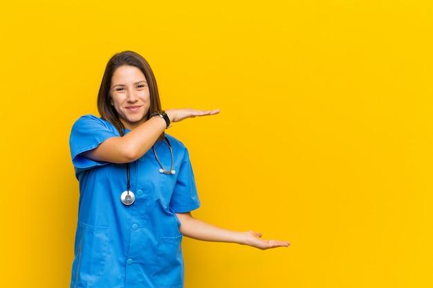 Trzymanie Przedmiotu Obiema Rękami Na Bocznym Copyspace, Pokazywanie, Oferowanie Lub Reklamowanie Przedmiotu Izolowanego Na żółto Premium Zdjęcia