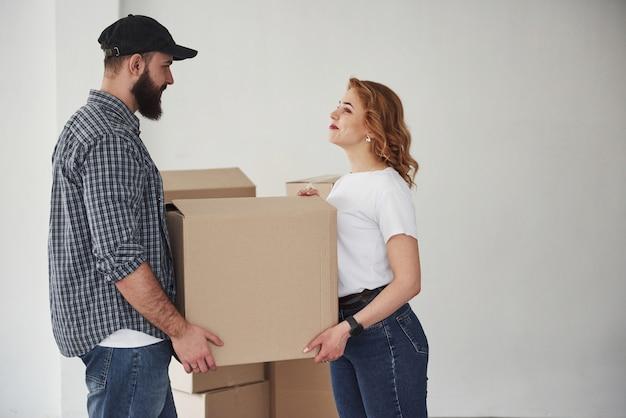 Trzymanie pudełka. szczęśliwa para razem w ich nowym domu. koncepcja ruchu