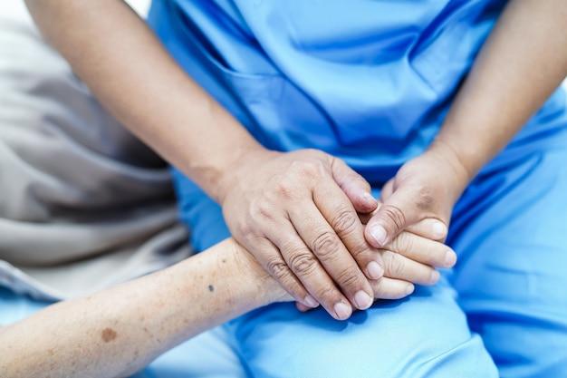 Trzymanie ręki azjatycki starszy lub starszy staruszka cierpliwy z miłością, troską, zachęcaniem i empat