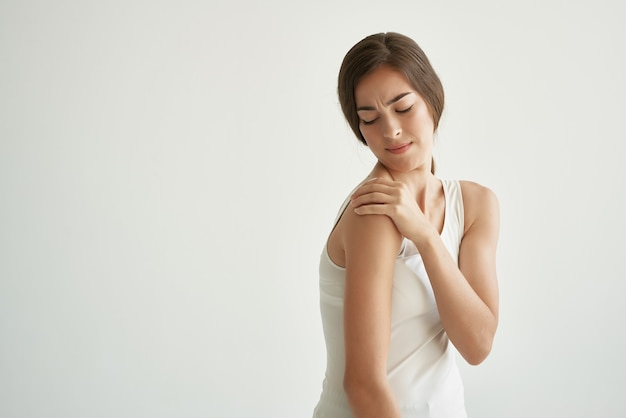 Trzymanie się za ramię w białej koszulce ból stawów reumatyzm
