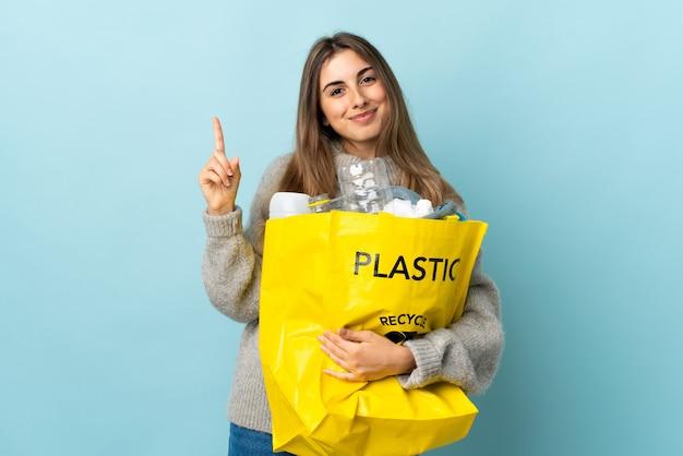 Trzymanie torby pełnej plastikowych butelek do recyklingu na odosobnionym niebieskim wskazaniu palcem wskazującym to świetny pomysł
