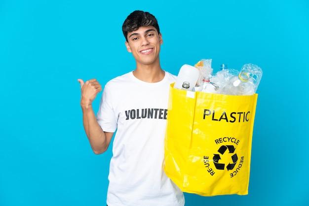 Trzymanie worka pełnego plastikowych butelek do recyklingu na niebieskiej ścianie skierowanej w bok, aby przedstawić produkt