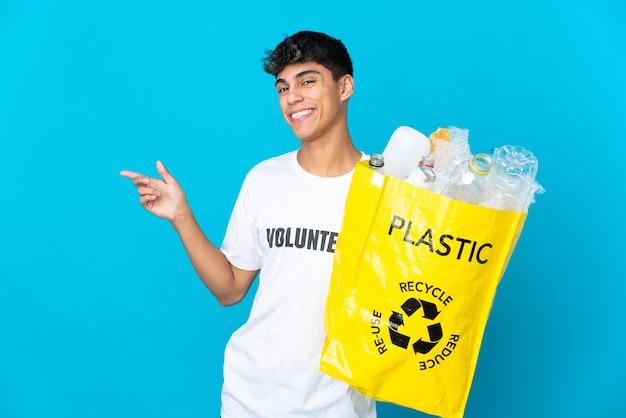 Trzymanie worka pełnego plastikowych butelek do recyklingu na niebieskiej ścianie, wskazując palcem w bok i prezentując produkt