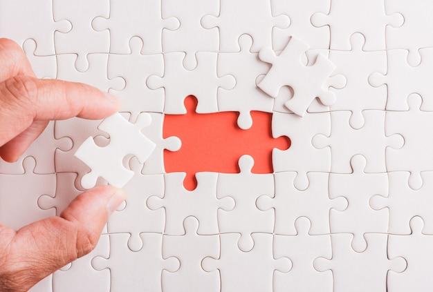 Trzymanie za rękę ostatniego kawałka układanki z białego papieru ostatnie elementy ułożone na miejscu, aby rozwiązać problem, wypełnij misję