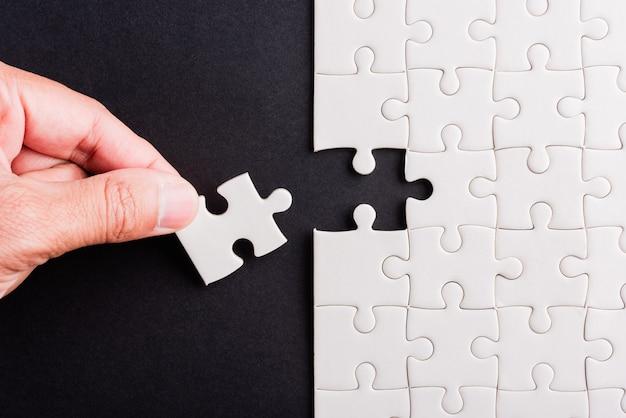 Trzymanie za rękę ostatniego kawałka układanki z białego papieru ostatnie elementy ułożone na miejscu, aby rozwiązać problem, zakończyć misję